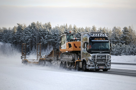 customized: PAIMIO, FINLAND - JANUARY 17, 2016: Customized Volvo FH16 750 with paintings and bull bar of Moto-Olli Oy hauls Liebherr R 918 crawler excavator on motorway in wintery conditions.