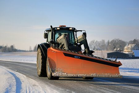 snow plow: SALO, FINLAND - JANUARY 16, 2016: Valtra tractor and FM snow plow on the road in South of Finland. In Finland, year 2016 begins with cold weather down to -30 degrees and snow alternating. Editorial
