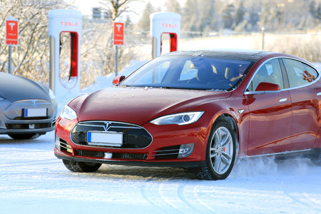supercharger: PAIMIO, FINLAND - JANUARY 17, 2016: Unidentified man drives red Tesla Model S at the snowy Supercharger Station Paimio. Unlike conventional cars, electric cars will always start in winter.
