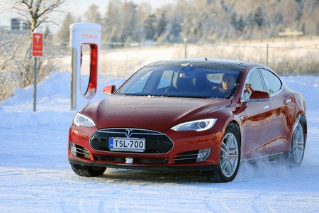 PAIMIO, FINLAND - JANUARY 17, 2016: Unidentified man drives red Tesla Model S at the snowy Supercharger Station Paimio. Unlike conventional cars, electric cars will always start in winter.