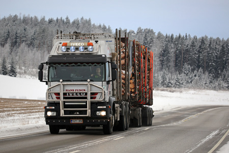 logging truck: SALO, FINLAND - JANUARY 22, 2016: Iveco Trakker 500 logging truck hauls pine on a winter afternoon in Salo. Iveco trucks for timber transport are a rare sight in Finland. Editorial