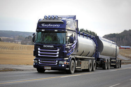 salo: SALO, FINLAND - JANUARY 31, 2016: Purple Scania R500 tank truck for bulk transport moves up hill on scenic road in Salo, Finland. Scania celebrates 125 years in 2016.