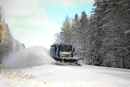 scenic highway: SALO, FINLAND - FEBRUARY 5, 2016: Scania truck equipped with snowplow clears a scenic highway in South of Finland. Destia takes care of the winter maintenance of the Finnish roads. Editorial