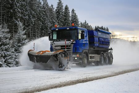plough machine: SALO, FINLAND - FEBRUARY 5, 2016: Scania truck equipped with snowplow clears a highway in South of Finland at dusktime. Destia takes care of the winter maintenance of the Finnish roads. Editorial