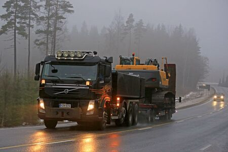 fm: SALO, FINLAND - FEBRUARY 6, 2016: Volvo FM truck hauls a Volvo crawler excavator on a foggy winter afternoon in South of Finland.