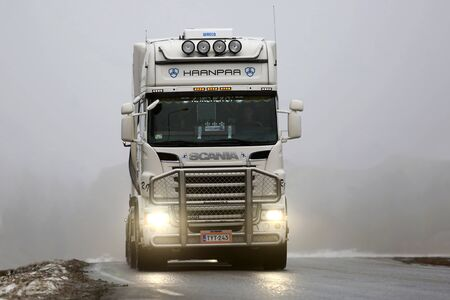 weather front: SALO, FINLAND - FEBRUARY 7, 2016: Front view of white Scania R500 tank truck on the road in heavy fog in South of Finland. Finnish weather conditions can be challenging for traffic in winter. Editorial