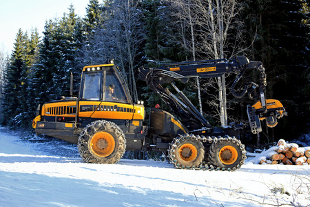 SALO, FINLAND -  FEBRUARY 27, 2016: Unnamed driver is about to begin harvesting with PONSSE Ergo forest harvester on a winter morning in South of Finland. The PONSSE Ergo is suited particularly for demanding harvesting conditions and steep slopes.