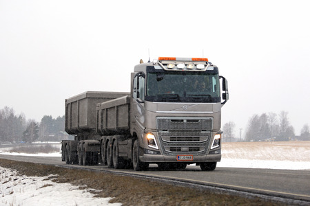 tipping: SALO, FINLAND - FEBRUARY 26, 2016: Bronze Volvo FH16 for limestone haulage on the road in snowfall in south of Finland. Editorial
