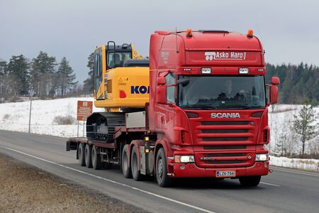 sensing: KARJAA, FINLAND - MARCH 5, 2016: Red Scania R500 hauls Komatsu PC 170LC excavator on lowboy trailer. The PC 170 LC uses Closed Center Load Sensing (CLSS) hydraulic system that improves fuel efficiency.