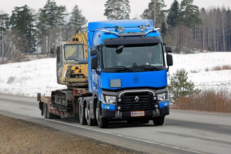 renault 5: KARJAA, FINLAND -  MARCH 5, 2016: Blue Renault Trucks T hauls tracked excavator on lowboy trailer. Renault Trucks aims to grow their market share in Finland.