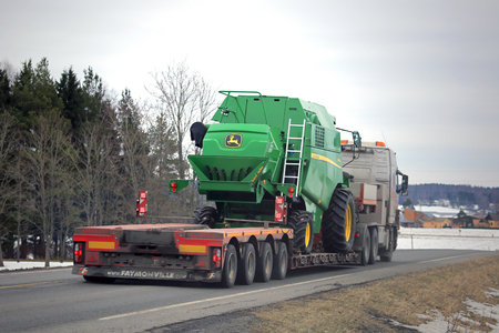 john deere: SALO, FINLAND - MARCH 4, 2016: Volvo truck hauls John Deere W330 combine harvester on lowboy trailer along highway. The W330 is a compact combine designed for farming in a smaller scale.