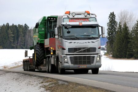 john deere: SALO, FINLAND - MARCH 4, 2016: Volvo FH16 truck hauls John Deere W330 combine harvester on lowboy trailer along highway. The W330 is a compact combine designed for farming on a smaller scale.