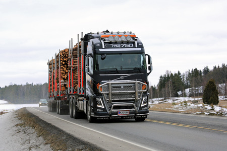 logging truck: SALO, FINLAND - MARCH 4, 2016: Volvo FH16 750 logging truck hauls pulp wood along highway. The new bioproduct mill of Metsa Group, currently under construction, is estimated to create 1500 new jobs.