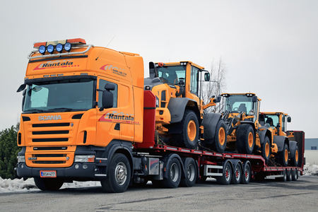 v8: LIETO, FINLAND - MARCH 12, 2016: Scania R500 V8 truck is ready to haul three Volvo L60H wheel loaders. The operating weight of Volvo L60H is 11.0-13.6 tonnes.