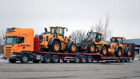 haul: LIETO, FINLAND - MARCH 12, 2016: Scania R500 V8 truck is ready to haul three Volvo L60H wheel loaders. The operating weight of Volvo L60H is 11.0-13.6 tonnes.