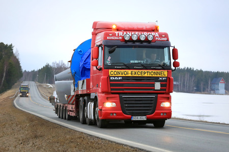 oversize load: SALO, FINLAND - MARCH 11, 2016: Red DAF XF 105 semi truck hauls industrial object as exceptional load in convoy with another similar transport. ELY Centre for Pirkanmaa issues permits for abnormal transports in Finland.