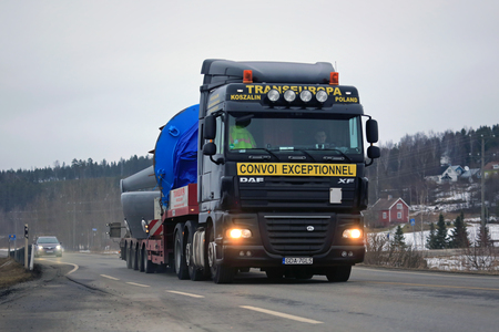 abnormal: SALO, FINLAND - MARCH 11, 2016: Black DAF XF 105 semi truck hauls industrial object as exceptional load along highway. ELY Centre for Pirkanmaa issues permits for abnormal transports in Finland.