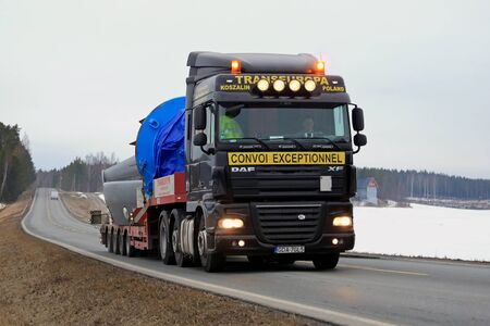 exceptional: SALO, FINLAND - MARCH 11, 2016: Black DAF XF 105 semi truck hauls industrial object as exceptional load along highway. ELY Centre for Pirkanmaa issues permits for abnormal transports in Finland.