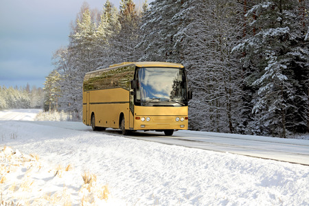 tour operator: Yellow coach bus travels along rural highway in winter landscape with snow. Copy space for your text. Editorial