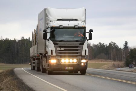 light duty: SALO, FINLAND - MARCH 24, 2016: White Scania truck and combination trailer moves along highway in South of Finland. The driver flashes the high beam lights briefly. Editorial
