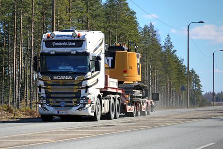 v8: LOUKKU, FINLAND - APRIL 2, 2016: Scania R560 V8 Truck hauls CAT 325F L Medium Hydraulic Excavator along highway.