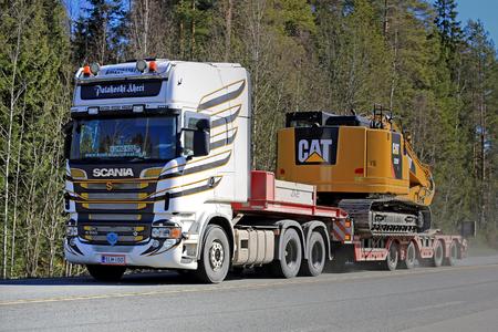 v8: FORSSA, FINLAND - APRIL 2, 2016: Scania R560 V8 Truck hauls CAT 325F L Medium Hydraulic Excavator along highway.