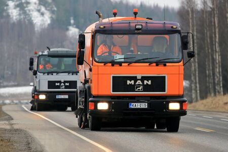 salo: SALO, FINLAND - MARCH 24, 2016: Two MAN Schorling Road Sweeper trucks drive along highway in Salo. Modern street sweepers are mounted on truck bodies and can vacuum debris that accumulates in streets.