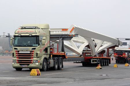 industrial drop: NAANTALI, FINLAND - APRIL 9, 2016: Scania R620 and industrial object on drop deck trailer as oversize load parked on asphalt yard. The length of the vehicle is 42 meters.