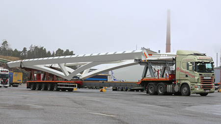oversize load: NAANTALI, FINLAND - APRIL 9, 2016: Scania R620 and long industrial object on drop deck trailer as oversize load. The length of the vehicle is 42 meters.