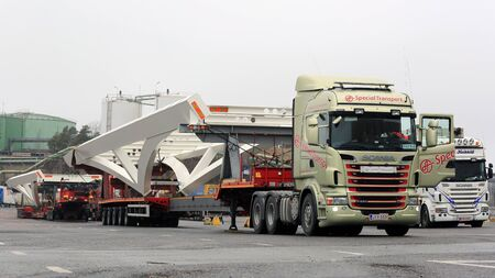 industrial drop: NAANTALI, FINLAND - APRIL 9, 2016: Scania truck driver detaches drop deck trailer with industrial object after oversize load transport.