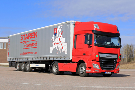 red truck: PAIMIO, FINLAND - APRIL 16, 2016: Red, new DAF XF Euro 6 semi truck and curtainsider trailer of Starek Transport parked at a truck stop in South of Finland. Editorial