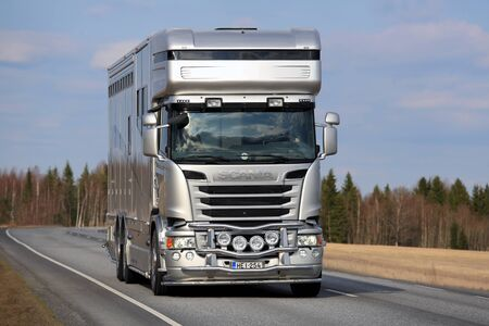 tl: KOSKI TL, FINLAND - APRIL 16, 2016: New  modern silver Scania horsebox for horse transport on the road at spring. Editorial