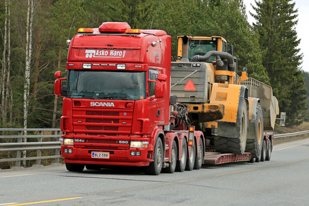 oversize load: FORSSA, FINLAND - APRIL 23, 2016: Scania 164G transports heavy Volvo L350F wheel loader as wide load along road in South of Finland. Editorial