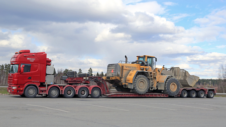 FORSSA, FINLAND - APRIL 23, 2016: Scania 164G truck stops at Forssa truck stop during the oversized transport of heavy Volvo L350F wheel loader, side view.