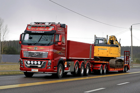 crawler: SALO, FINLAND - APRIL 22, 2016: Red Volvo FH16 750 transports New Holland crawler excavator on low bed trailer along highway on rainy evening in South of Finland.