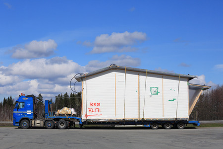 FORSSA, FINLAND - APRIL 23, 2016: Blue Volvo FH semi truck is to transport a prefabricated house module as oversize load in South of Finland. Editorial
