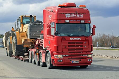 oversize load: FORSSA, FINLAND - APRIL 23, 2016: Scania 164G transports heavy Volvo L350F wheel loader as wide load in Forssa, Finland. Editorial