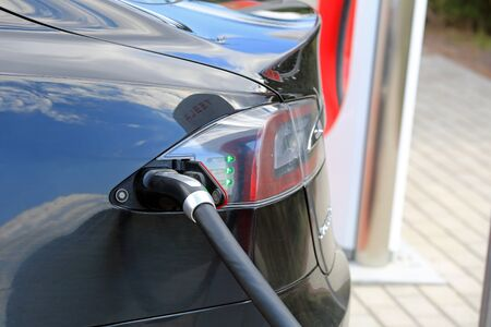 supercharger: PAIMIO, FINLAND - APRIL 29, 2016: Close up of black Tesla Model S electric vehicle being charged at Tesla Supercharger Station of Paimio. The green light shows the battery charging.