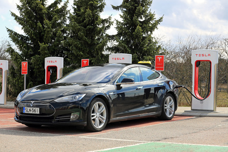 supercharger: PAIMIO, FINLAND - APRIL 29, 2016: Black Tesla Model S electric car which operates as taxi cab is being charged at Tesla Supercharger Station of Paimio.
