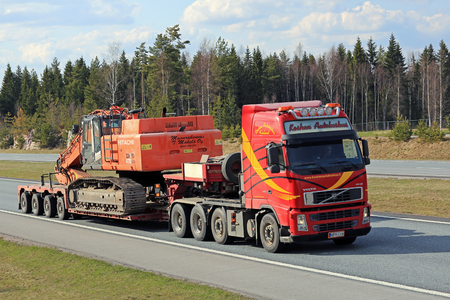 tonnes: SALO, FINLAND - APRIL 29, 2016: Volvo FH truck transports Hitachi Zaxis 470 lch crawler excavator on lowboy trailer along freeway. The Zaxis 470 LCH is a large excavator of ca 48 tonnes of operating weight. Editorial