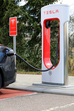 supercharger: PAIMIO, FINLAND - APRIL 29, 2016: Tesla Supercharger Station with black Tesla Model S electric vehicle being charged. Charging the battery from 10 to 80 percent takes about 40 minutes.