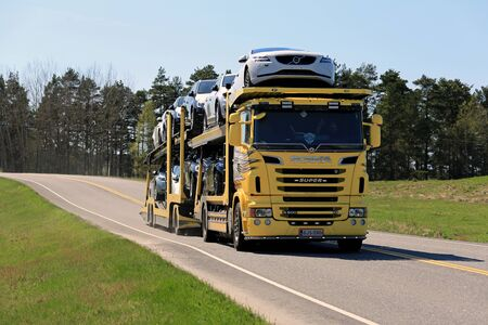 shipper: SALO, FINLAND - MAY 8, 2016: Yellow Scania R500 truck hauls a load of new cars along highway in South of Finland on a sunny day of spring. Editorial
