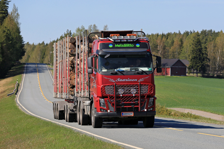 logging truck: SALO, FINLAND - MAY 8, 2016: Red Volvo FH16 600 logging truck transports timber logs along rural road on a sunny day of spring in south of Finland. Editorial