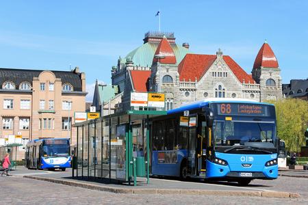 Helsinki, Finlandia - 12 maja 2016: Niebieski autobus VDL czeka na pasażerów na przystanku Dworzec Główny plac z Fiński Teatr Narodowy w tle w słoneczny dzień wiosny w Helsinkach. Publikacyjne