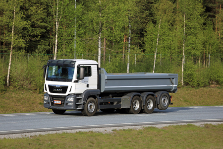 configured: SALO, FINLAND - MAY 13, 2016: White MAN TGS 35.480 tipper truck moves along freeway in South of Finland. The TGS is configured for heavy duty transport.