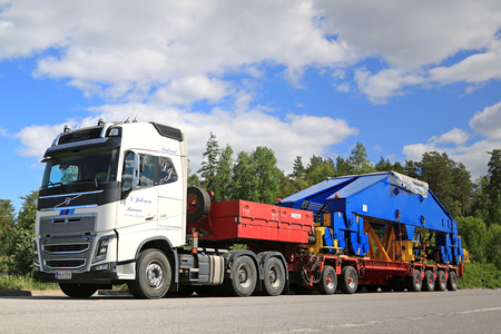bogie: PAIMIO, FINLAND - JUNE 4, 2016: White Volvo FH16 750 transports shipyard crane bogie on trailer. The 48-tonne load is supported by 24 wheels.