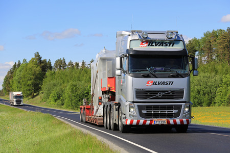 oversize load: SALO, FINLAND - MAY 27, 2016: Volvo FH transports an industrial object on lowboy trailer along highway in spring scenery. Editorial