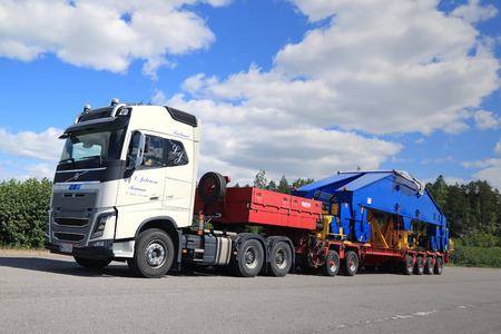 oversize load: PAIMIO, FINLAND - JUNE 4, 2016: White Volvo FH16 750 semi transports shipyard crane component on trailer. The 48-tonne load is supported by 24 wheels. Editorial