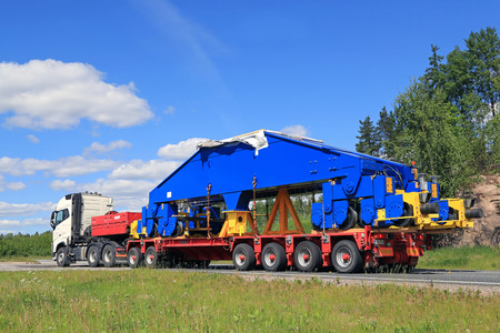 hauling: PAIMIO, FINLAND - JUNE 4, 2016: White Volvo FH16 750 transports a shipyard crane bogie on trailer. The weight of the load is 48 tonnes and it is supported by 24 wheels. Editorial