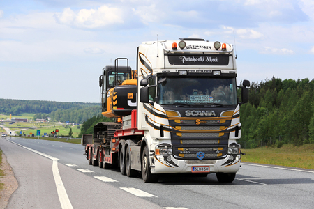 SALO, FINLAND - JUNE 3, 2016: Customized Scania R560 semi hauls JCB JS 210 LC hydraulic excavator along freeway on a clear day of summer in South of Finland. Editorial